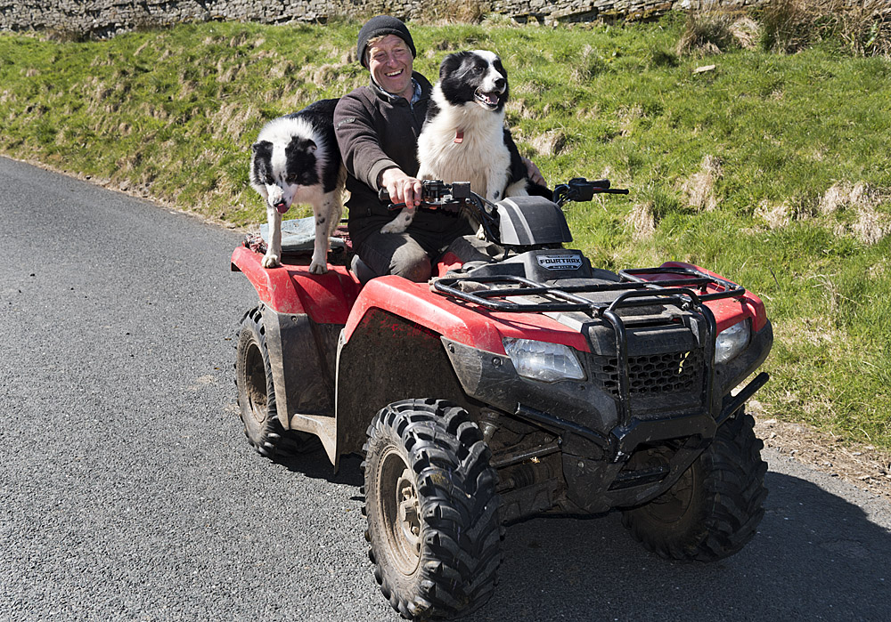 Farmer Raymond Calvert with two of his dogs, on his quad bike